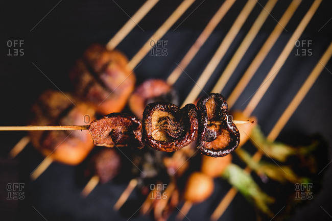 From above cooked hot mushroom skewer over table with delicious grilled skewers with meat, fish, squid and broccoli