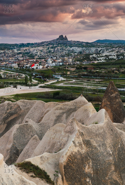 Peak of rough rock formation located in amazing countryside against overcast sky and distant city in Cappadocia, Turkey