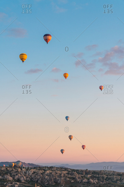 Many hot air balloons flying against mountain ridge and sunny sundown sky during festival in Cappadocia