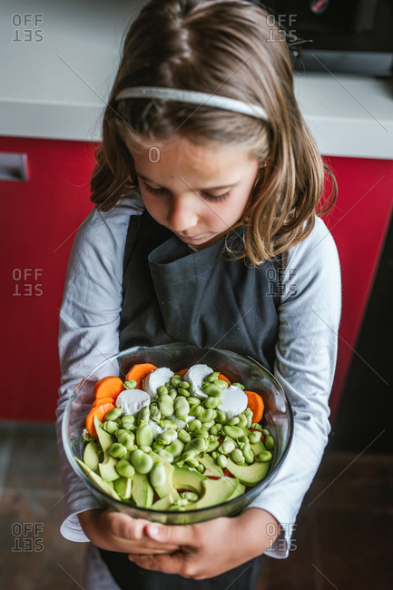 Little girl with bowl of healthy vegetable salad looking down while standing in kitchen at home