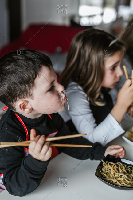 Boy and girl eating tasty noodles with vegetarian cutlets and vegetables while sitting at table at home