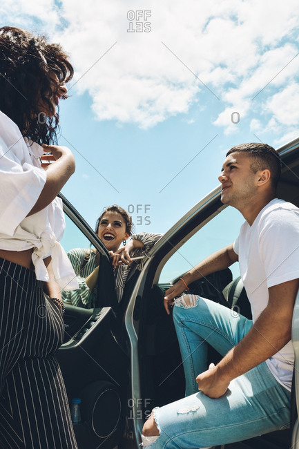 Group of friends enjoying a conversation outside the car. They talk and selfies in a tourist place