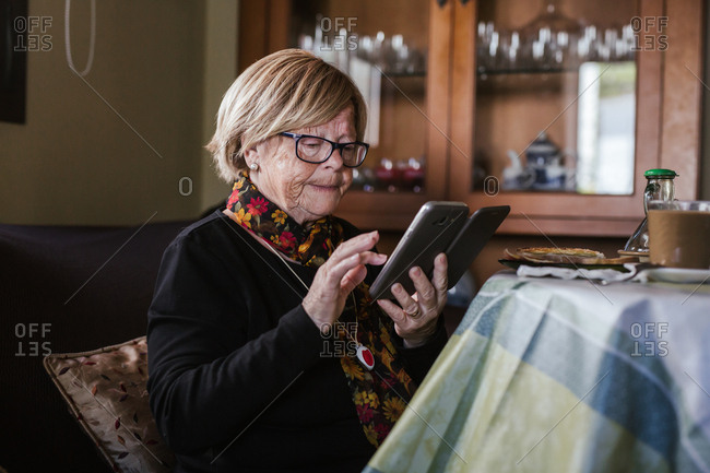 Senior woman looking and touching screen of smartphone while sitting on sofa in living room