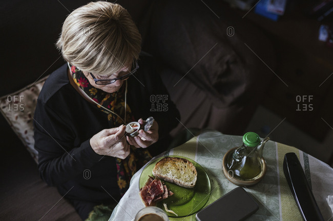 Senior attractive woman taking medication from pill box before breakfast