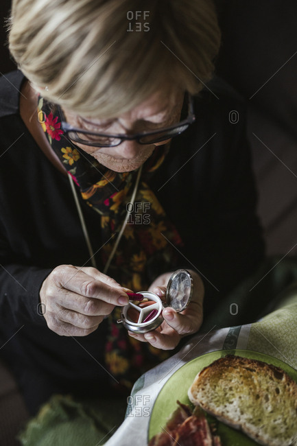 Hand of aged woman taking red pill from steel pill box