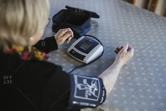 Unrecognizable senior female using tensiometer to measure blood pressure while sitting at table at home