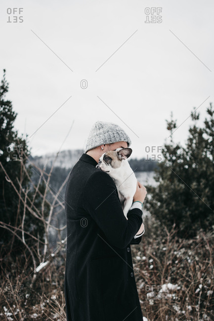 Side view of young woman in casual warm clothes hugging sad cute purebred puppy on mountain in nature