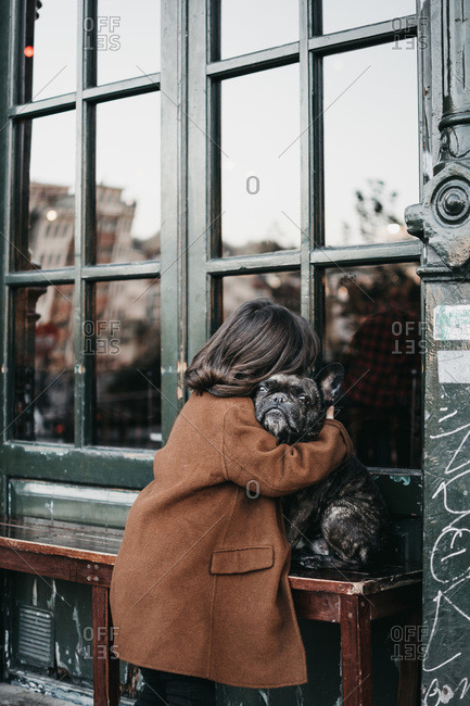 Cute little girl in casual warm coat hugging adult sad purebred dog on wooden bench on city street