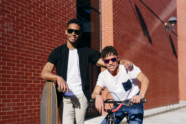 Young happy African American handsome men in casual clothes and sunglasses standing on street with bike and skateboard