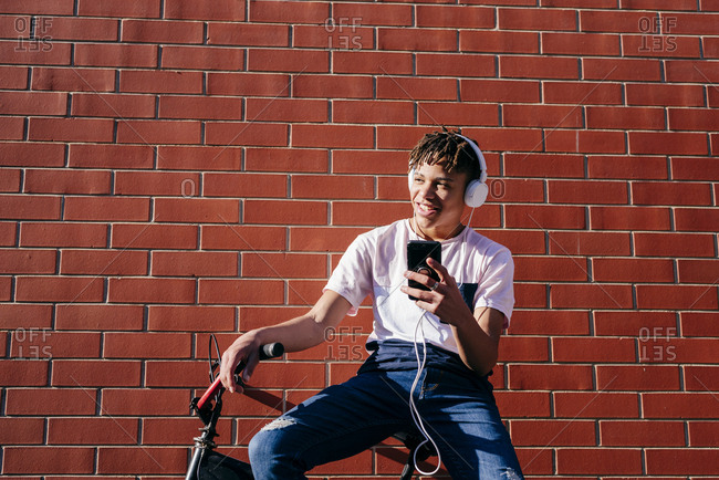 Young happy black male listening music with smartphone on bike
