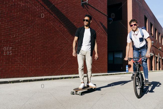 Young African American men riding bicycle and skateboard