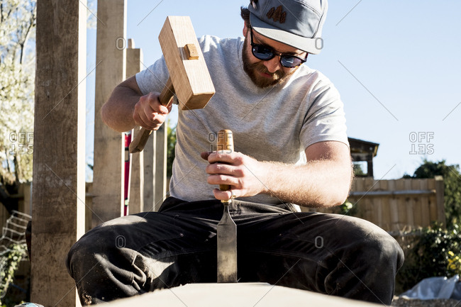 Man wearing baseball cap and sunglasses on building site, using mallet and chisel, working on wooden beam.