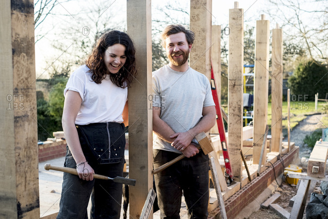 Smiling man and women holding hand tools standing on building site of residential building.