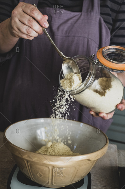 High angle close up of person pouring sugar into mixing bowl with baking ingredients.