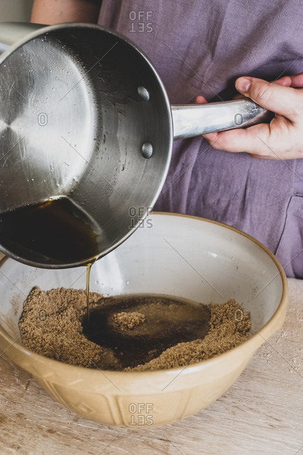 High angle close up of person pouring liquid into mixing bowl with baking ingredients.