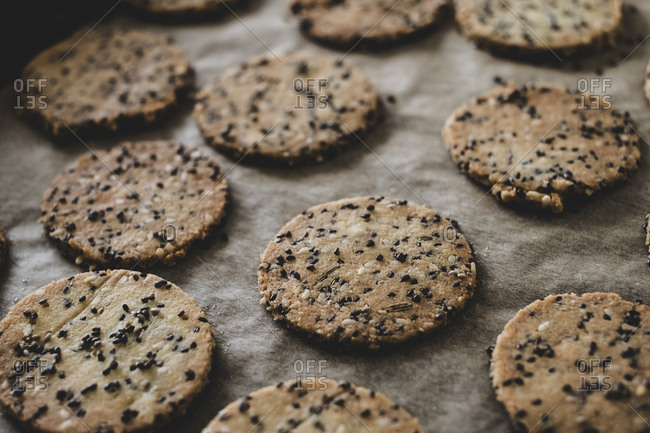 High angle close up of freshly baked seeded crackers on a baking tray.