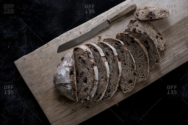 A loaf of fresh sliced brown bread on a bread board and a sharp knife