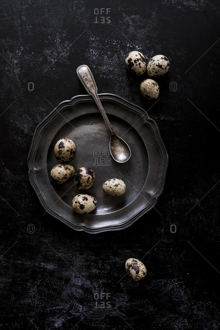 A pewter plate with small spotted quail's eggs and a spoon.