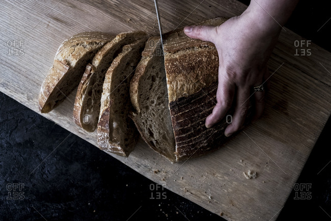 A hand holding a loaf of bread and using a breadknife to cut slices.
