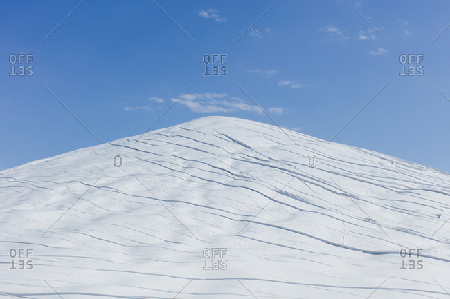 Manure heap covered with white tarpaulin, against a blue sky.