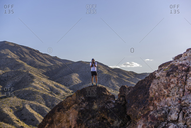 Young photographer capturing sunrise from top of mountain in desert