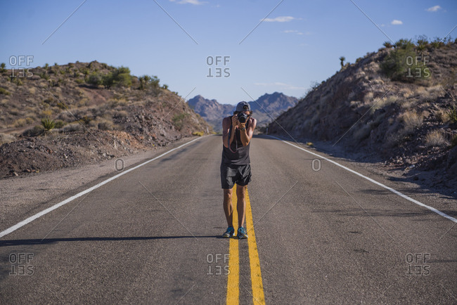 Travel photographer capturing with dslr in middle of mountain road