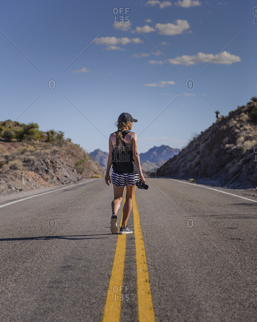 Young woman travel photographer walking in the middle of the road
