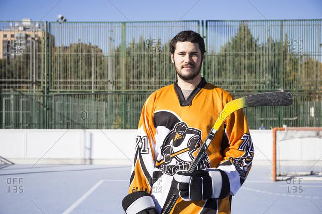 Hockey playing man in orange uniform standing with stick