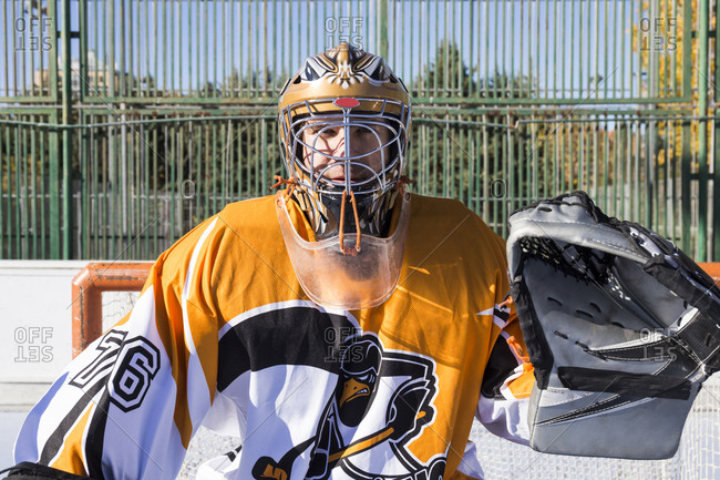 Goalkeeper man playing hockey standing in equipment on rink