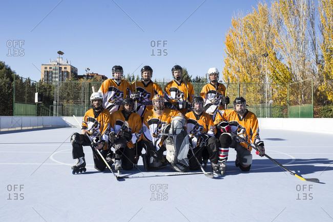 In-line hockey team in orange uniform posing on a rink in sunny day.