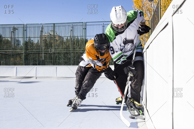 Two hockey players from opposite teams struggling for puck