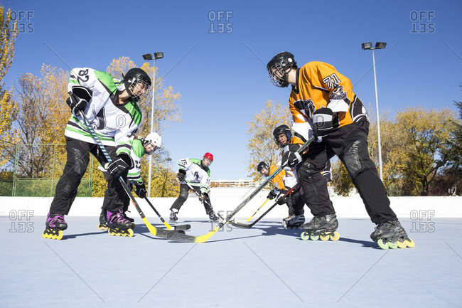 Side view of sportsmen standing prepared to play in-line hockey