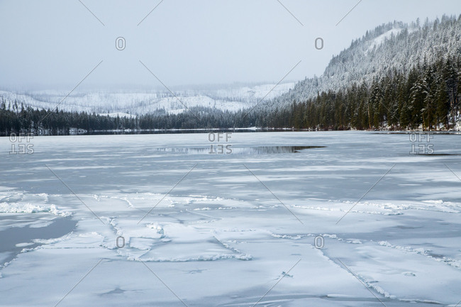 View of frozen lake and snow covered forest in the mountains