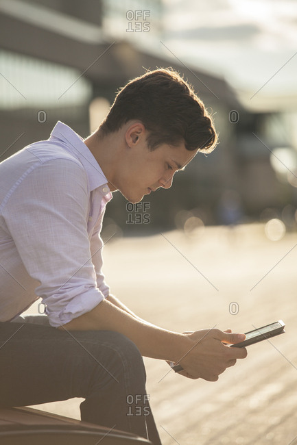 Male student in outdoor urban area studying on tablet