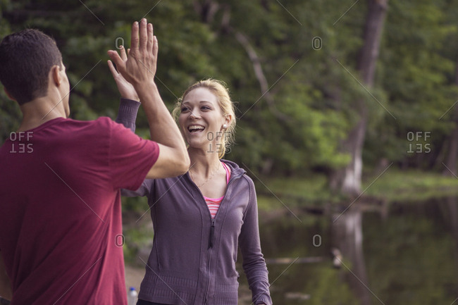 Friends high fiving each other during hike through forest