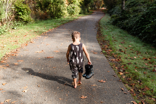 Child carries his rain boots on a trail