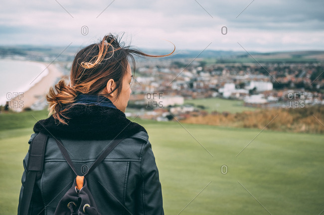 Woman looking from the top of a hill by the sea in autumn