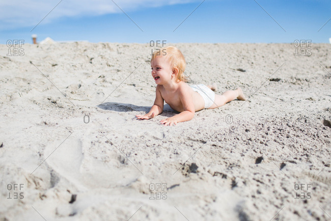 Blonde caucasian toddler smiling on sand dune in her diaper