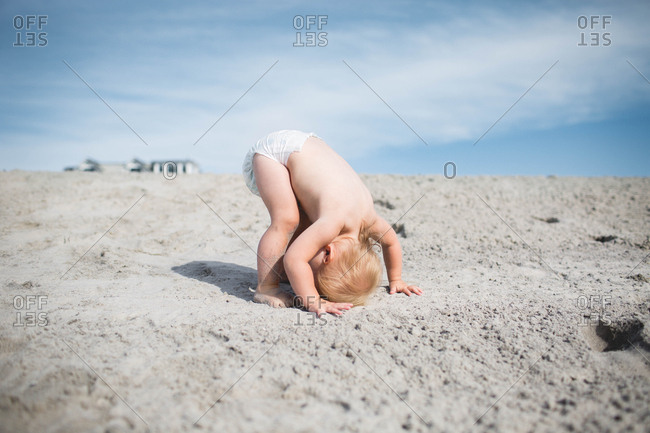 Toddler in diaper trying headstand on sand in avalon new jersey