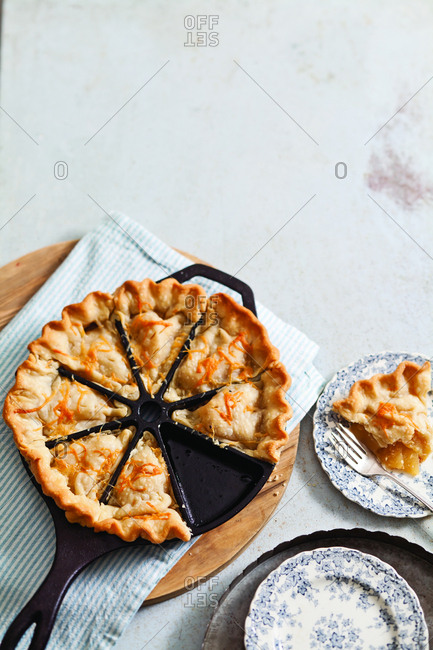 High angle view of apple pie in baking pan with plates on table at home