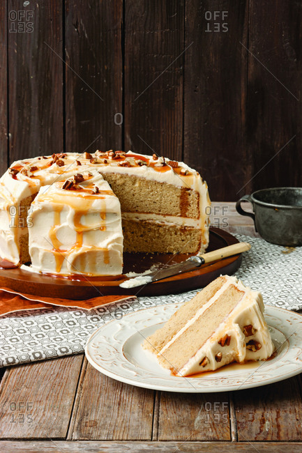 Apple cider cake on wooden table against wall at home