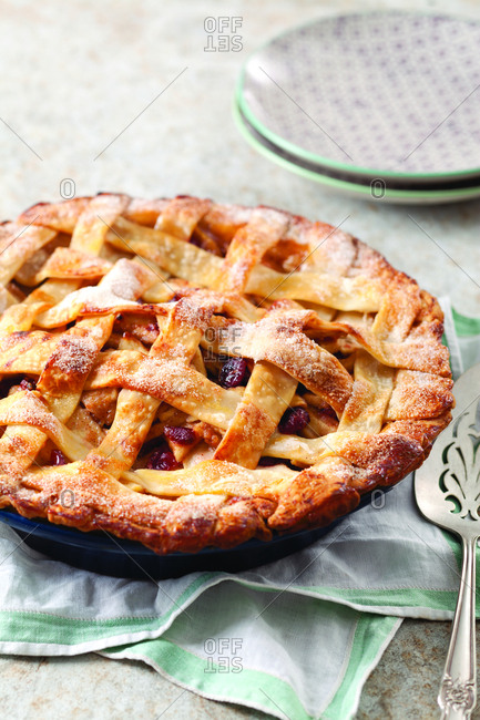 High angle view of apple cranberry pie served with spatula and napkin on table at home