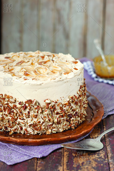 Close-up of butterscotch cake with spatula in plate on wooden table at home