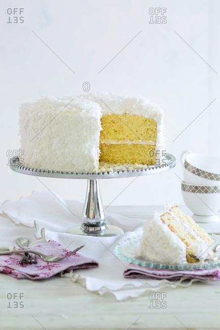 Cake on cake stand against white wall at home