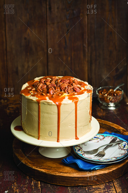 High angle view of caramel cake on cake stand against wooden wall at home