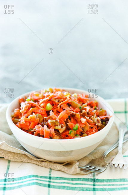Close-up of carrots slaw served in bowl with forks and napkins on table at home