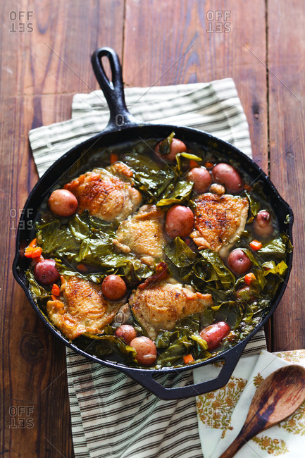 High angle view of cooked chicken with vegetables in saucepan on wooden table at home
