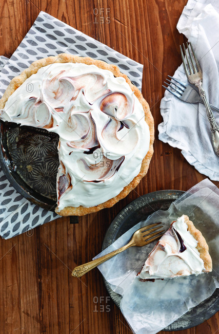 Overhead view of chocolate cream pie on wooden table at home