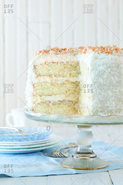 Close-up of coconut cake on cake stand against wall at home