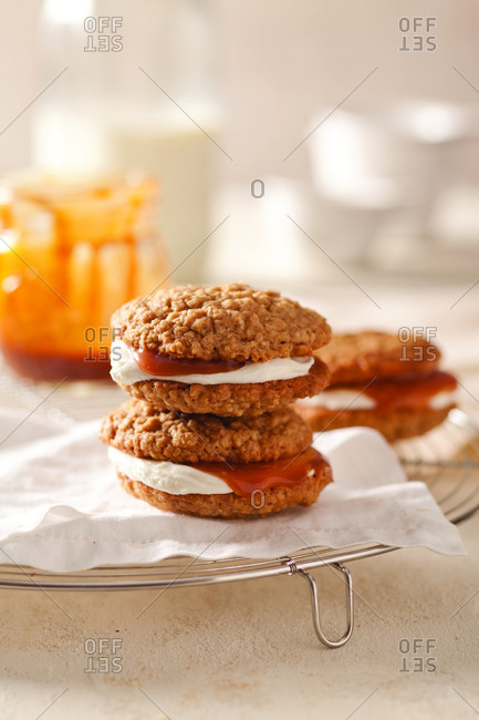 Close-up of cookie sandwiches with wax paper on cooling rack at home